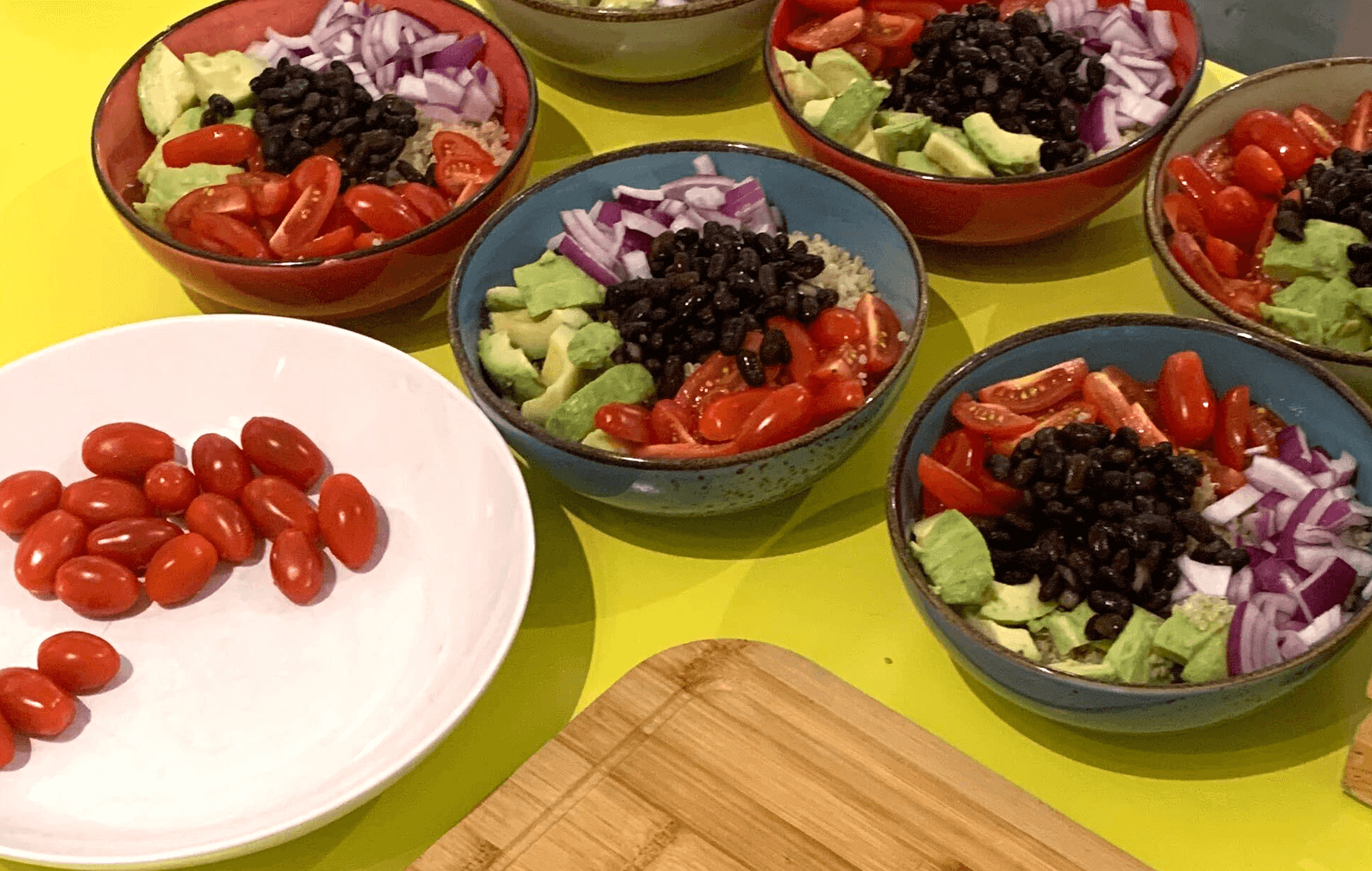 Some colorful bowls with freshly made Quinoa with cherry tomato, black beans, red onions and avocado.